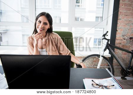 Hilarious employee is sitting in comfortable chair nearby workplace and looking at camera with bright wide smile. Portrait