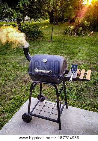 Port Charlotte, FL, USA - 04/28/2016: Garden smoker BBQ puffing out smoke