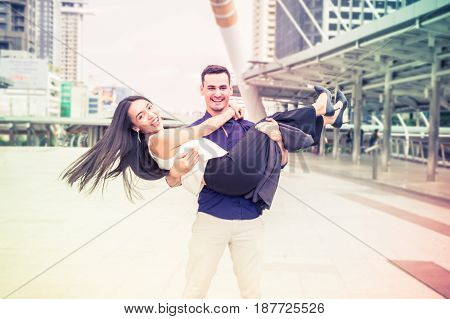 A young man carrying a girl in a business district.