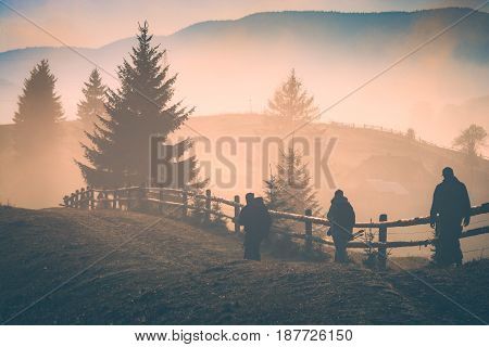 Group of people hikers walking on trail on the background of carpathian misty mountain valley. Instagram stylisation.
