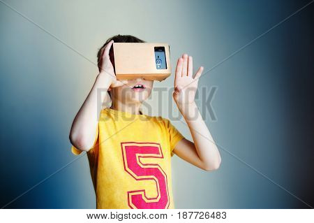 Little child uses virtual reality VR cardboard on blue background
