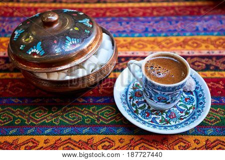 Traditional Turkish Coffee in a ceramic coffee mug on tablecloth traditional texture and pattern