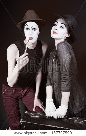 mimes woman and man with suitcase close up