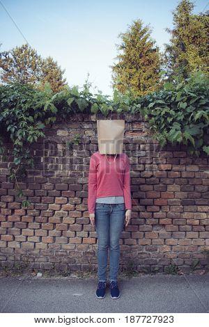 woman hiding under empty paper bag over brick wall