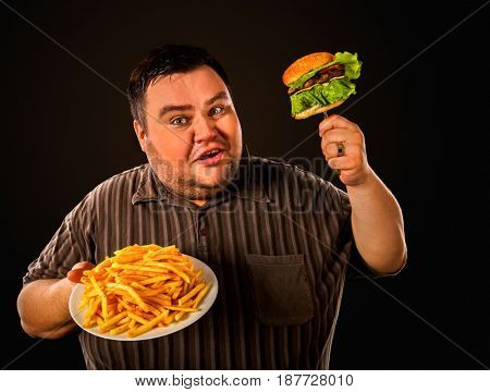 Diet failure of fat man eating fast food hamberger. Happy smile overweight person who spoiled healthy food by eating huge hamburger on fork. Junk meal leads to obesity. Advertising fast food.