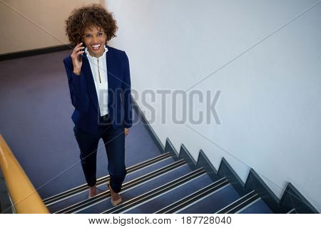 Businesswoman talking on mobile phone while walking upstairs in the office