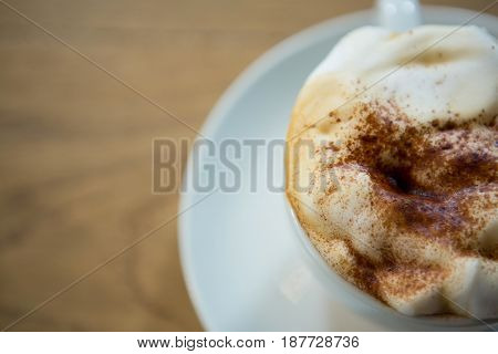 Overhead shot of coffee cup with creamy froth on table in cafeteria