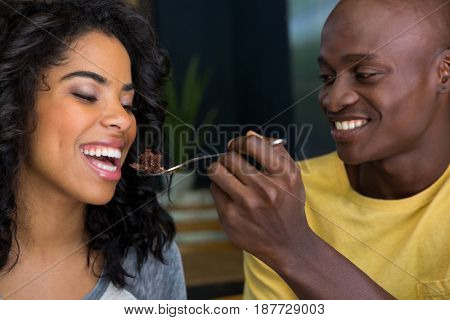 Loving young man feeding dessert to woman in coffee shop