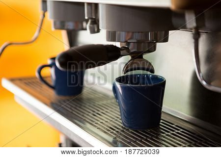 Close-up of machine making cup of coffee in cafe