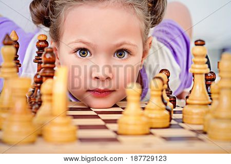 Little girl playing chess at home. Games and activities for children. Family concept.