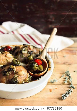 Roasted chicken meat with green olives and cherry tomatoes in a bowl, selective focus