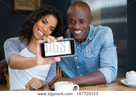 Smiling multi ethnic couple taking selfie with smart phone in coffee shop