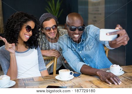 Cheerful multi ethnic friends wearing sunglasses while taking selfie in coffee shop