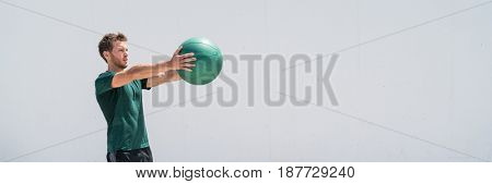 Banner. Medicine ball gym workout fitness man strength training arms doing front raise exercise for shoulder muscles. Upper body weighted ball workout at fitness center. Panorama crop with copy space.