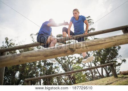 Man assisting woman to climb a hurdles during obstacle training at boot camp