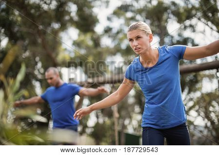 Fit man and woman during obstacle course training at boot camp