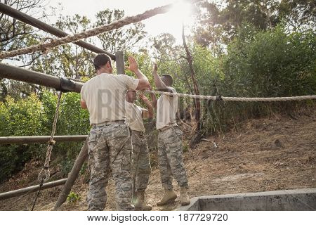 Young military soldiers giving after rope climbing during obstacle course at boot camp
