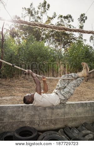 Young military soldier practicing rope climbing during obstacle course at boot camp