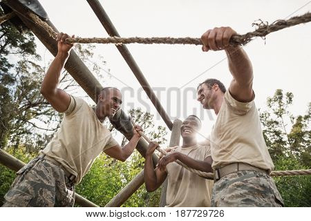 Military soldiers interacting during obstacle training at boot camp