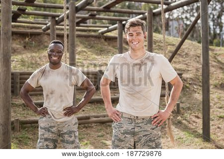 Portrait of military man standing with hand on hip during obstacle course in boot camp