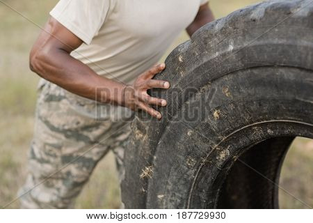 Mid section of military soldiers exercising with tyre in boot camp
