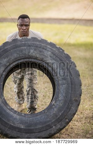 Determined military soldiers exercising with tyre in boot camp
