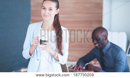Attractive woman sitting at desk in office having takeaway coffee