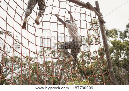 Military soldiers climbing a net during obstacle course in boot camp