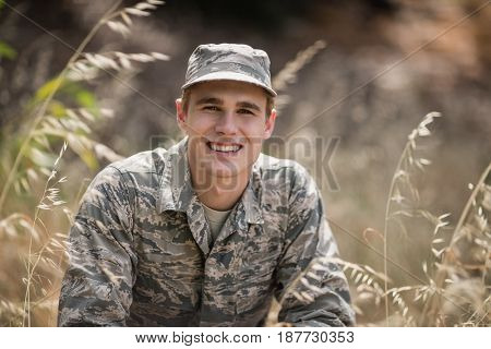 Portrait of happy military soldier crouching in grass in boot camp
