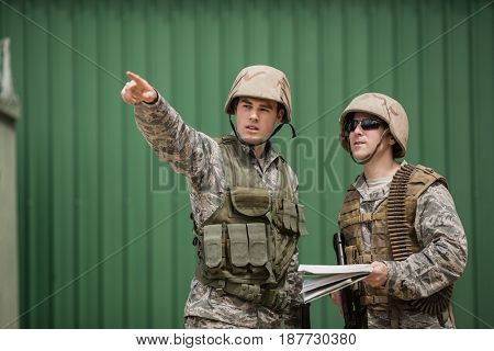 Soldiers showing direction to his colleague in boot camp