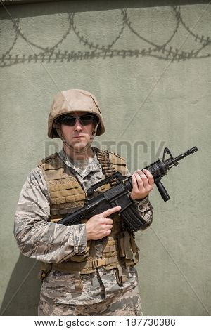 Military soldier standing with a rifle in boot camp