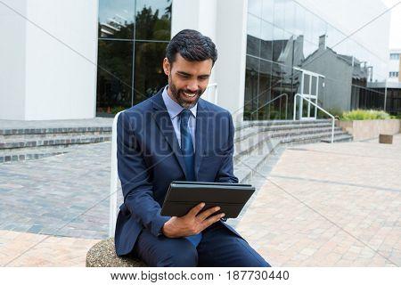Smiling businessman using digital tablet in the office premises