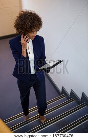 Businesswoman talking on mobile phone while using digital tablet in the office