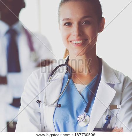 A smiling female doctor with a folder in uniform indoors