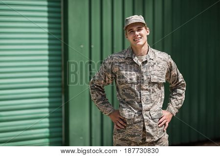 Portrait of smiling military soldier standing with hands on hip in boot camp