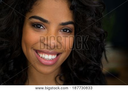 Close-up portrait of smiling young woman in coffee shop