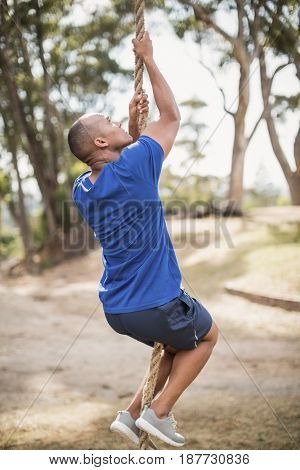 Fit man climbing rope during obstacle course in boot camp