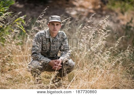 Portrait of military soldier crouching in grass in boot camp