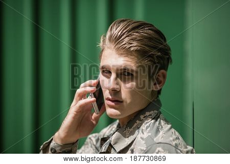 Portrait of military soldier talking on mobile phone in boot camp