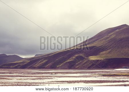 Beautiful Icelandic landscape. Green volcanic mountains in cloudy weather.