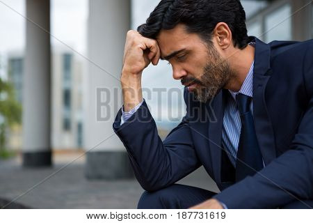 Depressed businessman sitting with hand on forehead in the office premises