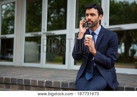 Businessman holding disposable coffee cup talking on mobile phone in conference centre