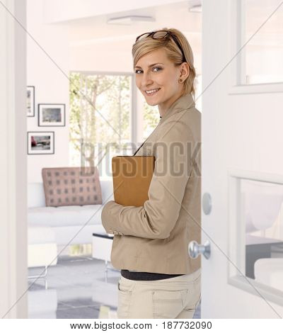 Happy casual caucasian blonde businesswoman standing at home doorway, wearing glasses, folder in hand. Smiling, standing, looking at back camera.