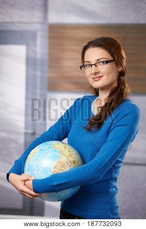 Portrait of young female student in glasses, holding globe, looking at camera, smiling.