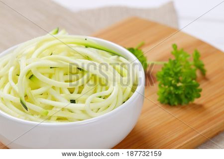 bowl of raw zucchini noodles on wooden cutting board - close up
