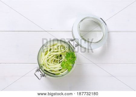 jar of raw zucchini noodles on white wooden background