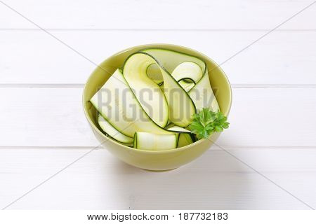 bowl of raw zucchini strips on white wooden background
