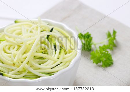 bowl of raw zucchini noodles on beige place mat - close up
