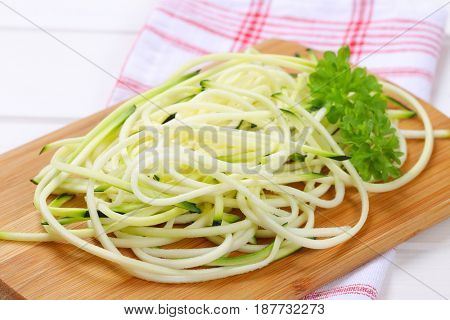 heap of raw zucchini noodles on wooden cutting board - close up