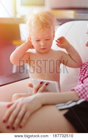 One year old baby boy with his mother looking at smartphone screen. Indoor portrait